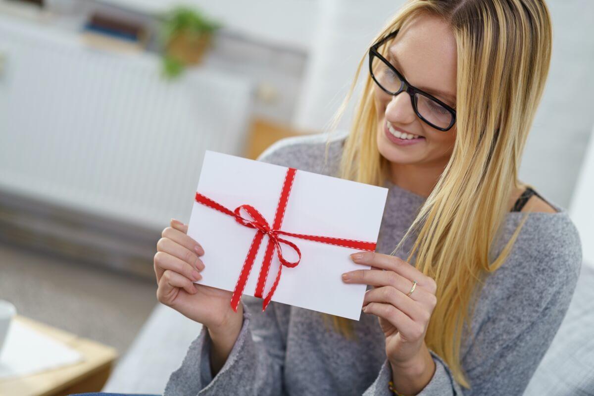 Frau packt Geschenkgutschein für Massage aus